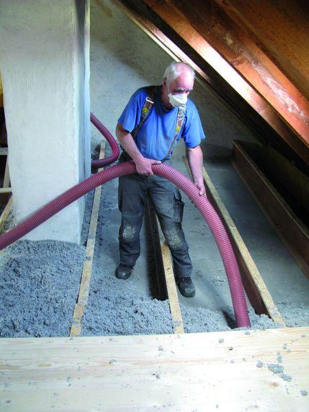 Isofloc- Fachbauleiter Rolf Wittmann füllt den Hohlraum unter den Dielen mit dem umweltfreundlichen Dämmstoff aus.